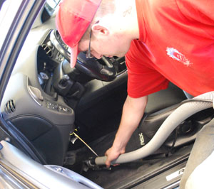 Photo of a man vacuuming the floor of a car.
